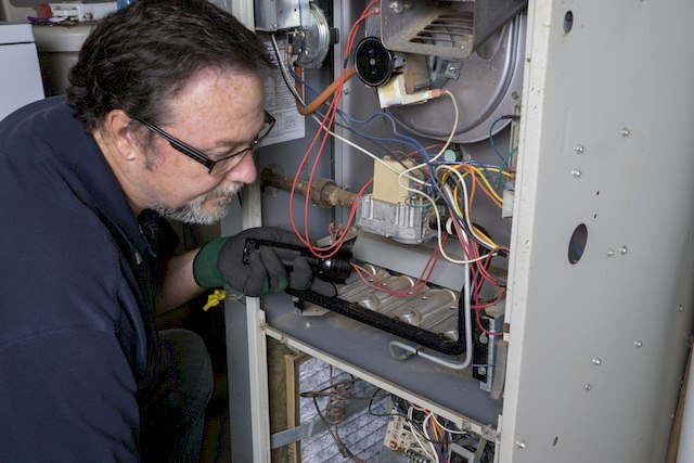 Repairman Inspecting a Furnace (Furnace Maintenance and Safety Tips for the Fall)