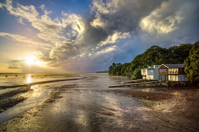 image - A coastal home on a beach with low tide during the sunset