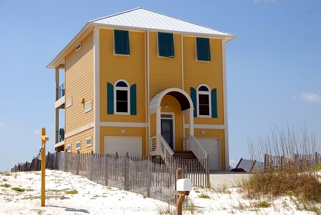 image - A yellow beach home with blue wind shutters